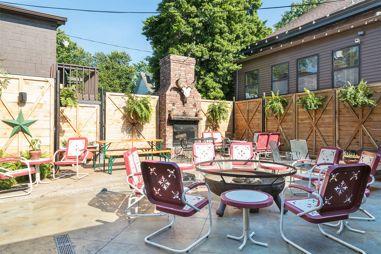 Outdoor Patio of Urban Cowboy's Public House. Bench seats and table/chairs are scattered. A stone fireplace is set up towards the back.