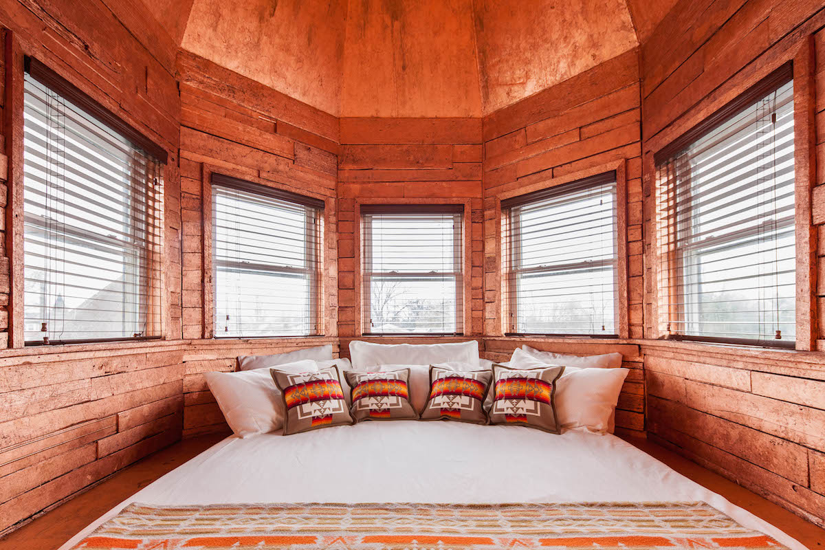 Bedroom space of The Tower room inside Urban Cowboy Nashville. A king sized bed takes up most of the space, with a set of small pillows lining the head. The ceiling is domed and windows line along each wall.