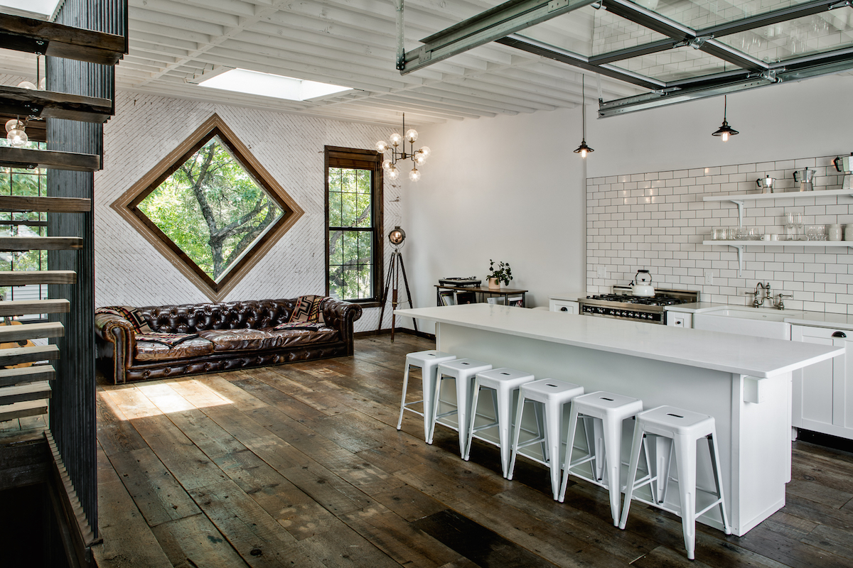 View from slightly under the stairwell, showing a common area of the Private Townhouse/Treehouse of Urban Cowboy Brooklyn. Five stools are stacked next to a white bartop, with an oven and range area just beyond. A large couch is just nearby.