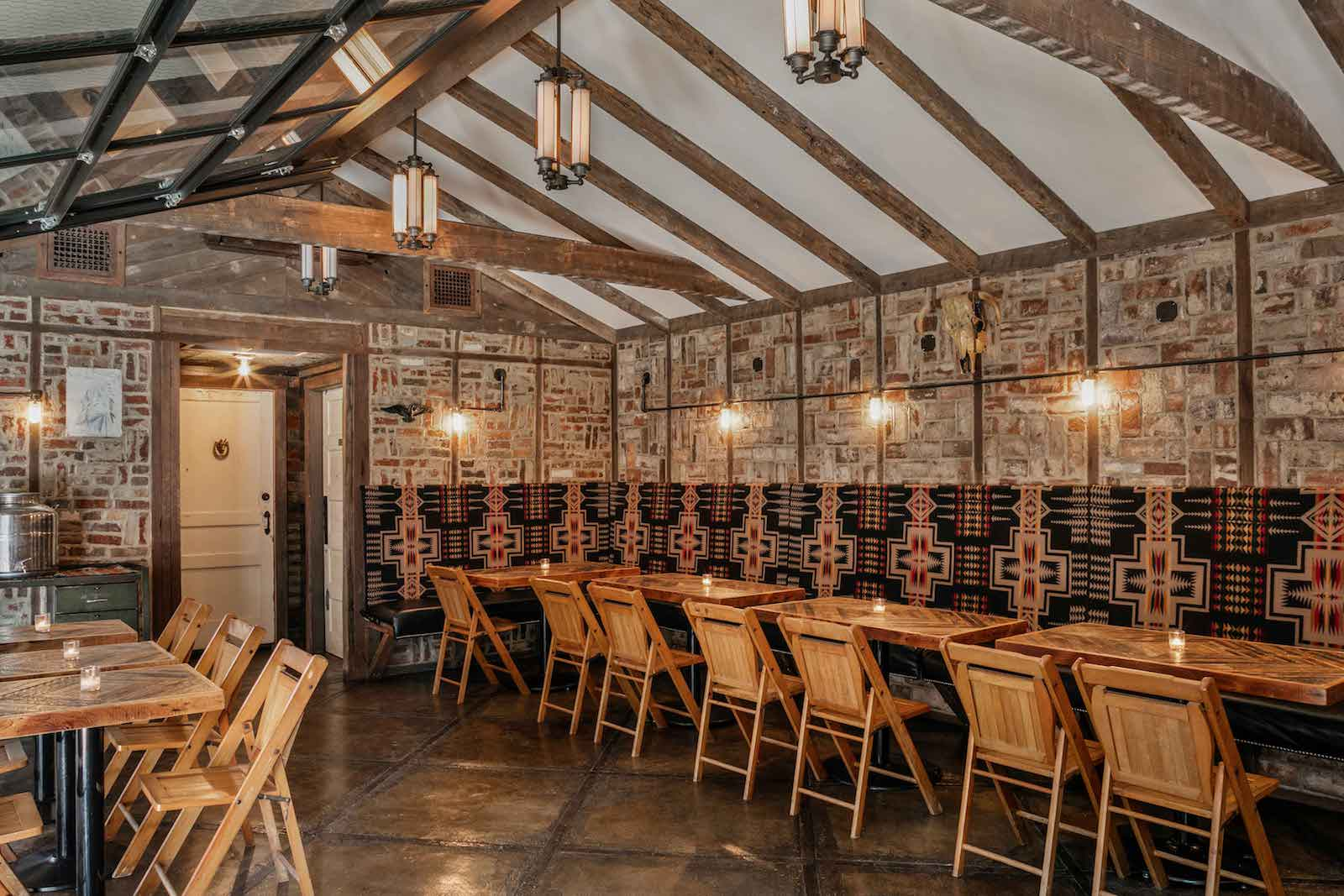 View of the main dining area of Urban Cowboy's Public House Kitchen and Bar. Wooden tables and chairs/benches make up this main dining area.