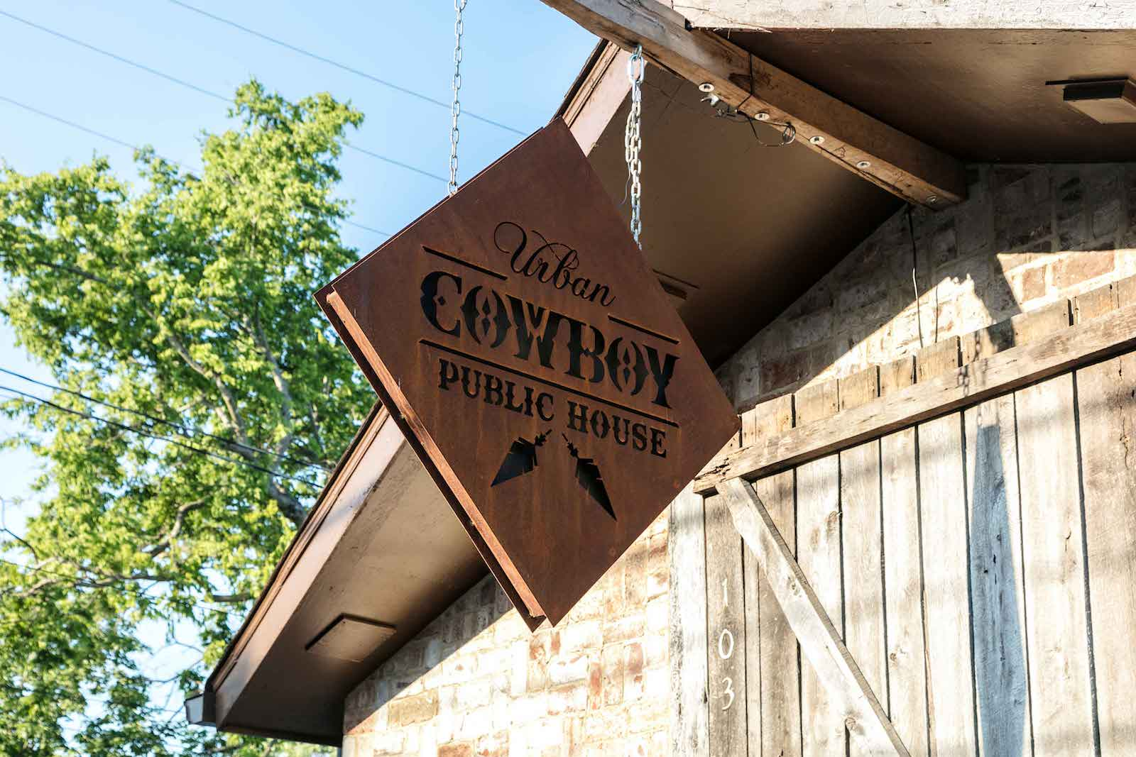 A diamond sign hanging outside the Public House of Urban Cowboy Nashville.