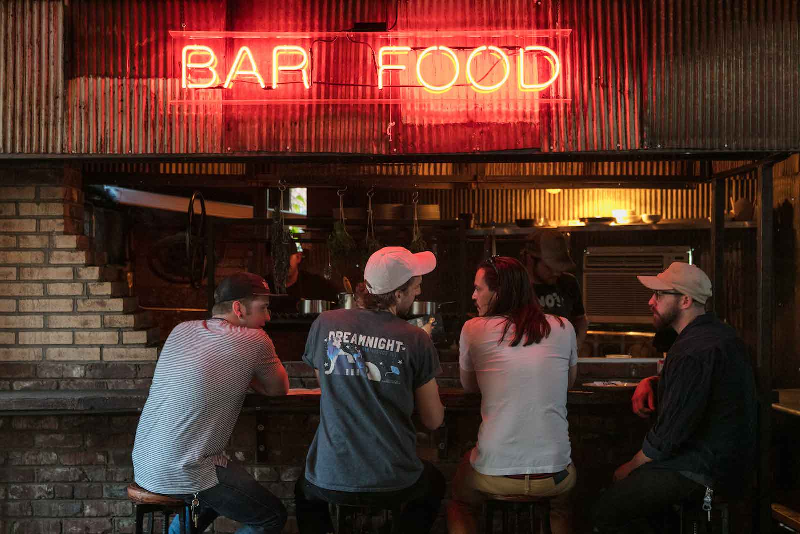 A set of three out for a night at Urban Cowboy's Public House Bar. A neon sign above the bar stools reads