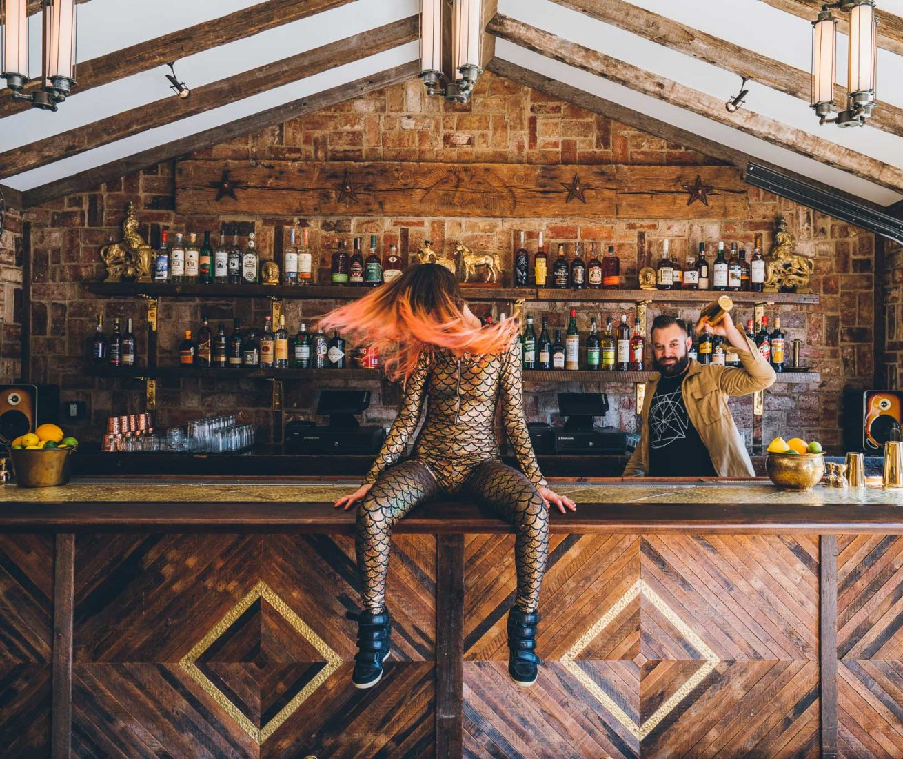 Orange haired dancer whipping her hair while seated on the bar of Public House. Photo by Dave Krugman.