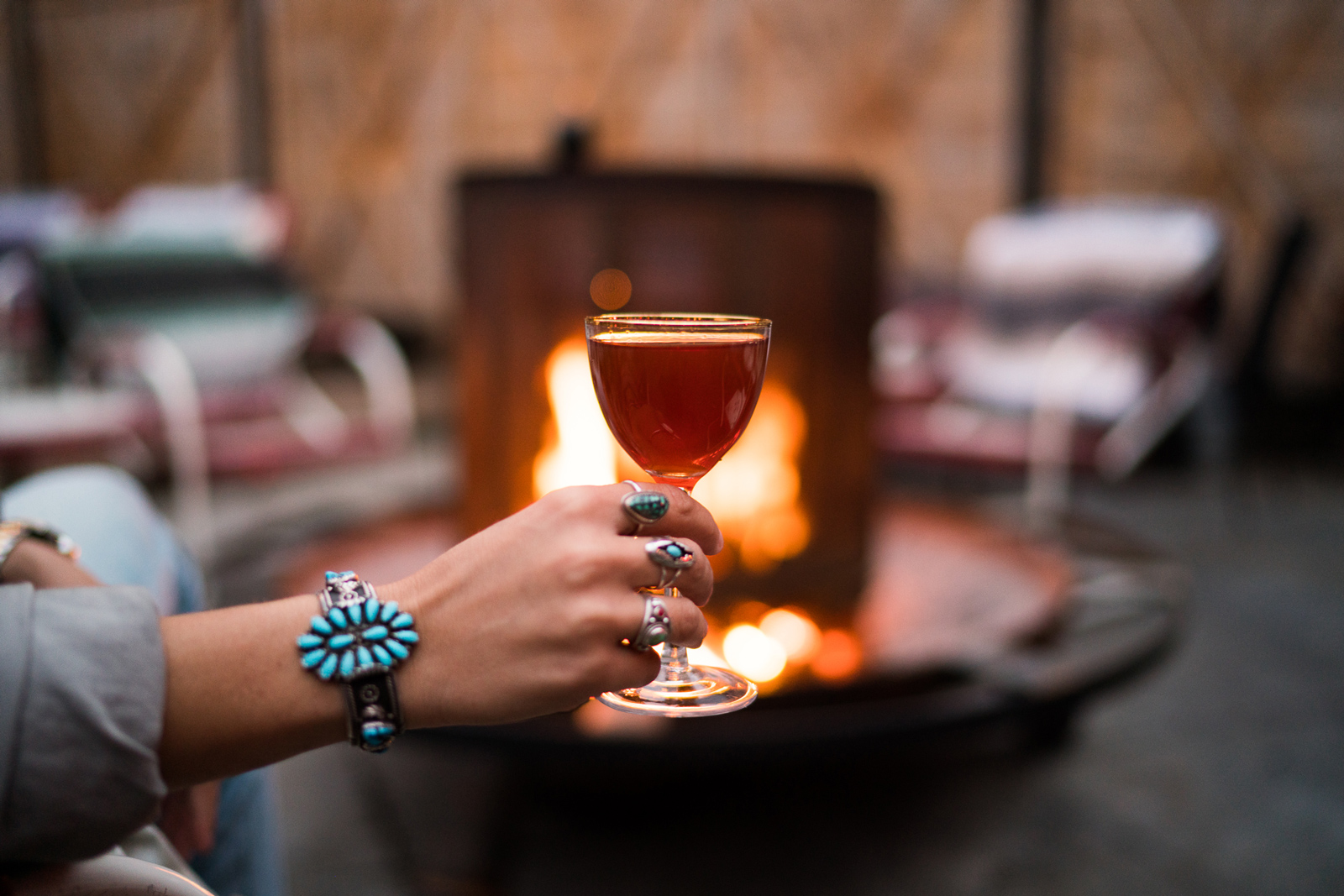 Urban Cowboy guest holding drink by the fire. This drink is served from Public House